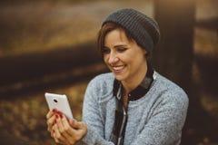 Portret van gelukkige, het glimlachen vrouwenzitting alleen in het bos met smartphone Millenialmeisje die sociale media spelen stock foto