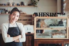 Portret van gelukkige jonge bedrijfseigenaar met de achtergrond van de koffiewinkel stock afbeelding