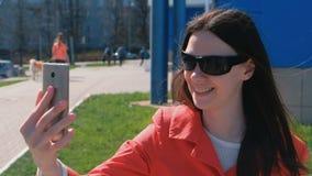 Portret van gelukkige jonge donkerbruine vrouw in zonnebril die op video spreken die de telefoon naast de blauwe bouw op uitnodig stock footage