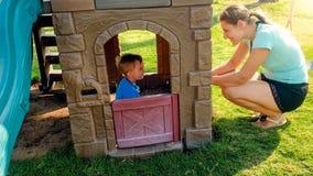 Portret van gelukkige jonge moeder die haar lachende peuterjongen bekijken die in stuk speelgoed huis bij speelplaats spelen stock afbeelding