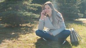 Portret van gelukkige jonge mooie vrouwenzitting in het de lentepark op het gras en het spreken op een mobiele telefoon stock video