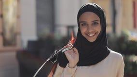 Portret van gelukkige jonge moslimvrouw die in hijab de straat met het winkelen zakken in haar hand terugtrekken zich Online Wink stock video