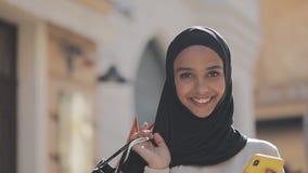 Portret van gelukkige jonge moslimvrouw in hijab die zich met smartphone onderaan de straat met het winkelen zakken in haar hand  stock video