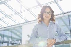 Portret van gelukkige jonge onderneemster die op traliewerk in bureau leunen Stock Foto's