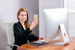 Portret van gelukkige jonge succesvolle onderneemster op kantoor Zij zit bij de lijst en maakt selfies Black Friday of Cyber-Maan stock afbeeldingen