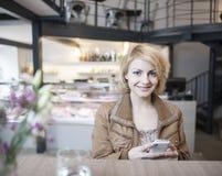 Portret van gelukkige jonge vrouw die celtelefoon in koffie met behulp van Royalty-vrije Stock Foto's
