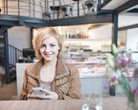 Portret van gelukkige jonge vrouw die celtelefoon in koffie met behulp van Royalty-vrije Stock Foto