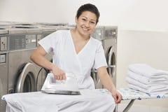 Portret van gelukkige jonge vrouw het strijken kleren in Laundromat Royalty-vrije Stock Foto