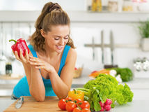 Portret van gelukkige jonge vrouw klaar om plantaardige salade te maken Stock Foto