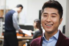 Portret van gelukkige jonge zakenman in het bureau Stock Afbeeldingen
