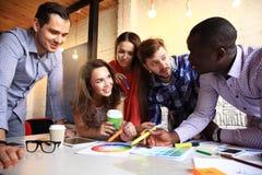 Portret van gelukkige jongeren in een vergadering die camera en het glimlachen bekijken Jonge ontwerpers die aan a samenwerken stock afbeelding