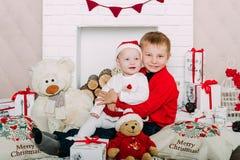 Portret van gelukkige kinderen met de dozen en de decoratie van de Kerstmisgift Twee jonge geitjes die pret hebben thuis Stock Afbeelding