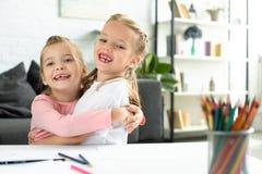 portret van gelukkige kleine kinderen die elkaar koesteren bij lijst met documenten en potloden voor tekening stock afbeelding