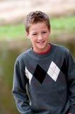 Portret van gelukkige leuke jongen in sweater voor een vijver stock foto's