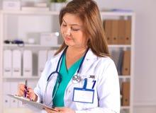 Portret van gelukkige medische artsenvrouw in bureau Stock Afbeelding