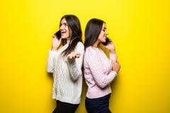Portret van gelukkige meisjes die op mobiele die telefoons spreken over gele achtergrond worden geïsoleerd royalty-vrije stock afbeeldingen