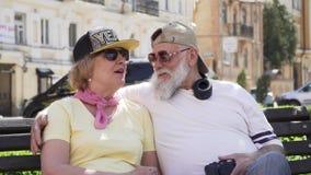 Portret van gelukkige modieuze oude mensen die op de bank in de stad ontspannen stock footage