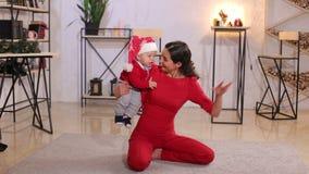 Portret van gelukkige moeder en aanbiddelijke baby in kostuum van Kerstman stock footage