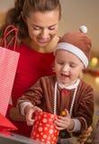 Portret van gelukkige moeder en baby het openen Kerstmis huidige doos Stock Fotografie