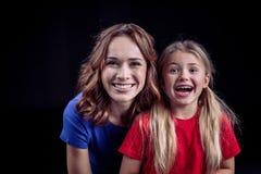 Portret van gelukkige moeder en dochter die bij camera glimlachen stock foto's