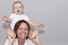 Portret van gelukkige moeder en haar 2 jaar zoon Grappige peuterzitting op de moedershals en het bekijken camera Stock Afbeeldingen