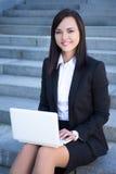 Portret van gelukkige mooie bedrijfsvrouwenzitting op treden en Stock Foto's