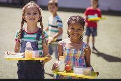 Portret van gelukkige schoolmeisjes die maaltijd in dienblad houden stock foto's