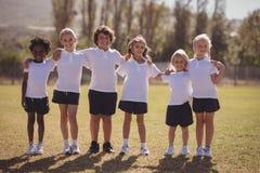 Portret van gelukkige schoolmeisjes die zich met wapens rond in park bevinden stock fotografie