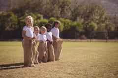 Portret van gelukkige schoolmeisjes die zich in zak tijdens ras bevinden stock foto's