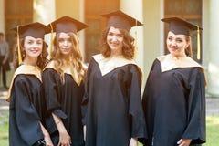 Portret van gelukkige studenten in graduatietoga's royalty-vrije stock fotografie