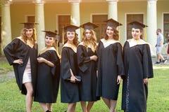 Portret van gelukkige studenten in graduatietoga's stock foto
