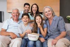 Portret van gelukkige uitgebreide familie die op TV in woonkamer letten Stock Fotografie