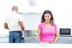 Portret van gelukkige vrouw met echtgenoot het helpen in keuken Royalty-vrije Stock Afbeeldingen