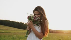 Portret van gelukkige vrouw in witte kleding die zich op gebied met boeket van bloemen bevinden die in camera glimlachen stock videobeelden
