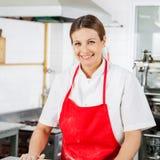 Portret van Gelukkige Vrouwelijke Chef-kok In Red Apron Stock Afbeelding