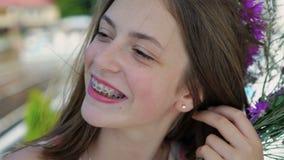 Portret van gelukkige vrouwelijke tiener die met steunen op tanden bij camera glimlachen 4K stock footage