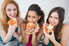 Portret van gelukkige vrouwelijke vrienden die pizza thuis eten Stock Foto