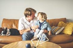 Portret van gelukkige zoon met vader thuis stock afbeeldingen