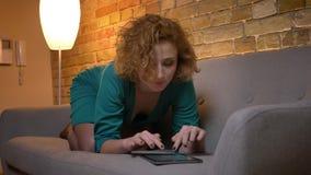Portret van gember hethaired Kaukasische meisje liggen op bank en het letten op in tablet aandachtig op comfortabel huis stock videobeelden