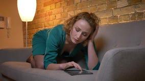 Portret van gember hethaired Kaukasische meisje liggen op bank en het letten op in tablet zorgvuldig op comfortabel huis stock video
