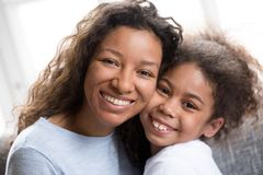 Portret van gemengde van de rasmamma en dochter omhelzing thuis royalty-vrije stock afbeeldingen