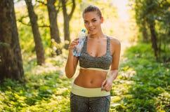 Portret van geschiktheidsvrouw in het hout met een fles water S Stock Afbeelding