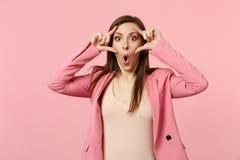 Portret van geschokte jonge vrouw die jasje dragen die mond open die, het uitrekken zich oogleden houden op pastelkleur roze muur stock foto's