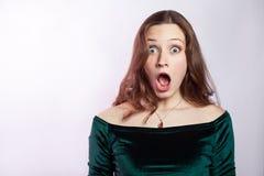 Portret van geschokte vrouw met sproeten en klassieke groene kleding stock foto's