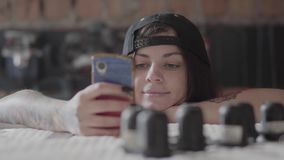 Portret van getatoeeerd hipster meisje die een bericht in smartphone op de achtergrond van een workshop met details typen stock video