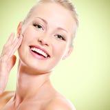 Portret van gezonde glimlachende vrouw wat betreft gezicht Royalty-vrije Stock Foto
