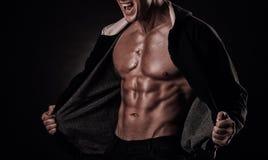 Portret van gillende bodybuilder met strakke spieren en zijn mou stock foto's