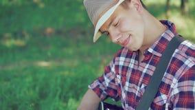 Portret van gitarist in hoed die de gitaar in zonnig groen park spelen 4K stock footage