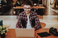 Portret van Glimlachen Freelancer die aan Laptop werken stock afbeeldingen