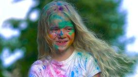 Portret van glimlachend blond meisje met kleurstof op haar gezicht die de camera bekijken en het heilige poeder werpen stock video